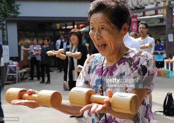 An elderly woman works out with wooden dumbbells in the grounds of a temple in Tokyo on September 21 to celebrate Japan's Respect for the Aged Day...