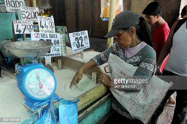 An elderly women buys rice at a market in Manila on August 5 2014 Philippine inflation shot up to a nearly threeyear high of 49 percent in July the...