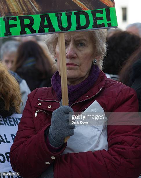An elderly women protests outside a Madrid court where exBankia president Miguel Blesa was giving evidence relating to the collapse of the Spanish...