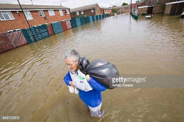 An elderly women rescues possessions in Toll Bar near Doncaster UK flooded in the June 2007 unprecedented summer floods | Location Toll Bar near...