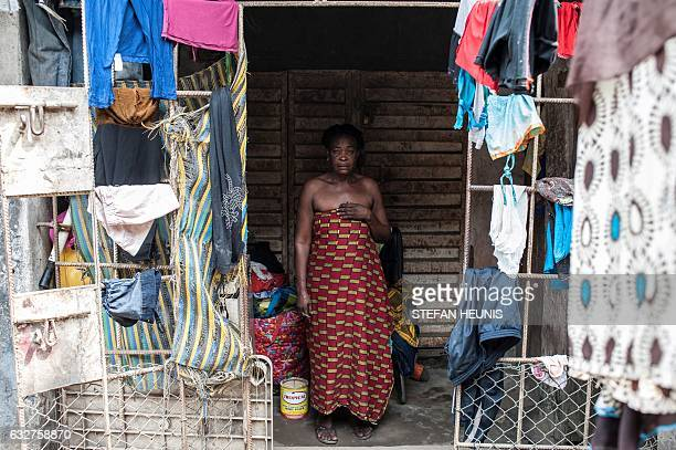 An elderly women stands in front of her one bedroom accommodation in Lagos on January 6 2017 Nearly two years after taking office Nigeria's President...
