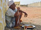 An elderly Yemeni refugee eats a meal on April 13 2015 at a refugee boarding facility run by the UN High Commission for Refugees at Obock a small...