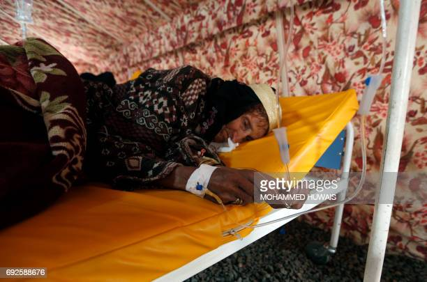An elderly Yemeni woman suspected of being infected with cholera receives treatment at a makeshift hospital in Sanaa on June 5 2017 Yemen is...