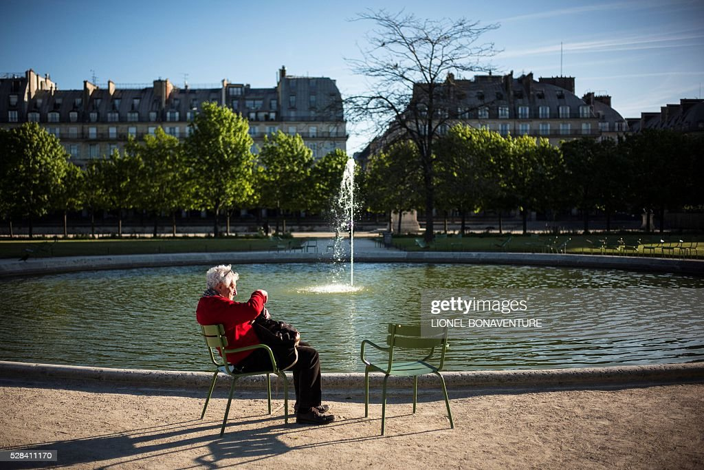 An eldery man enjoys the sun at the Tuileries garden on May 5, 2016 in Paris. / AFP / LIONEL