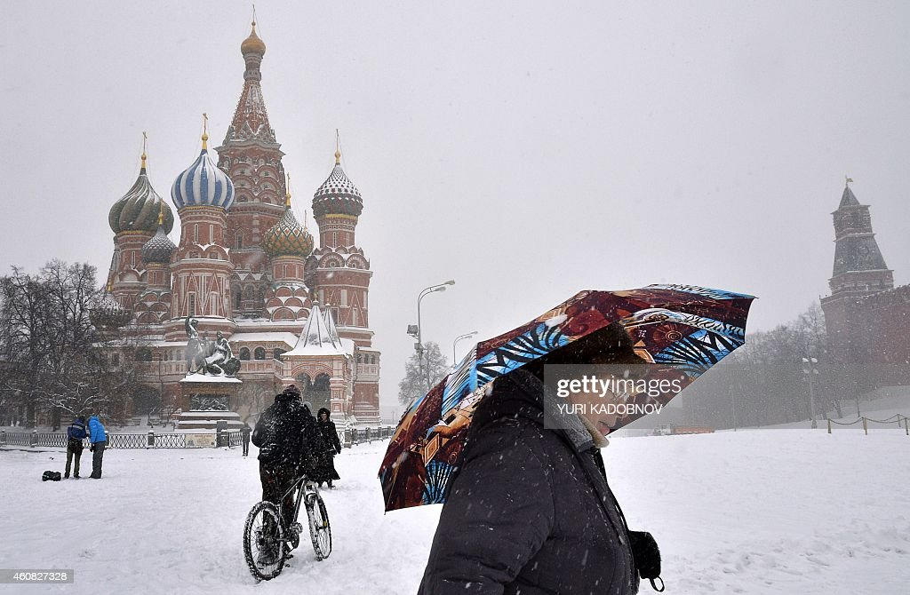 An eldery woman walks with an umbrella under the snow past St Basil's Cathedral on Moscow's Red Square on December 25 2014 AFP PHOTO / YURI KADOBNOV