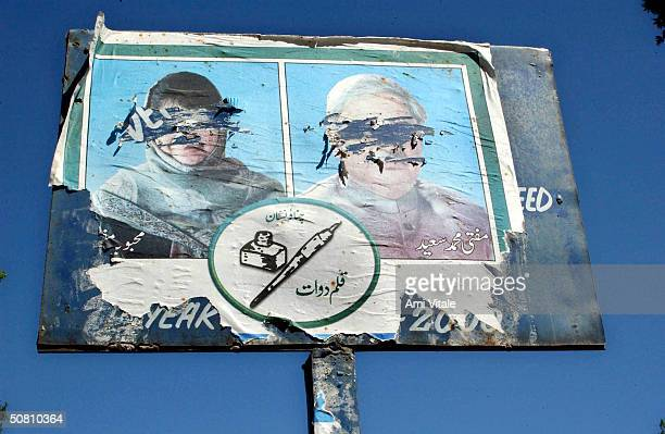 An election campaign poster of Chief Minister Mufti Mohammed Sayeed and his daughter Mehbooba Mufti with their faces scratched out stands in Anatanag...