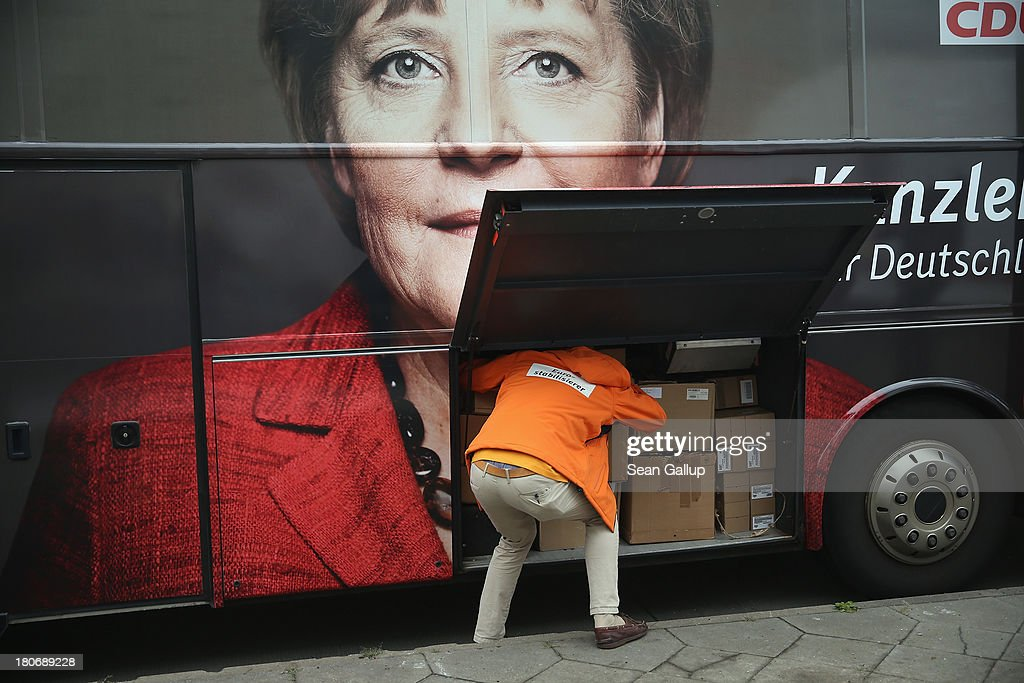 An election campaign worker pulls boxes from an election campaign bus that depicts German Chancellor and Chairwoman of the German Christian Democrats (CDU) Angela Merkel outside CDU headquarters on September 16, 2013 in Berlin, Germany. Germany faces federal elections on September 22 and so far the CDU has a strong lead in polls over the opposition.