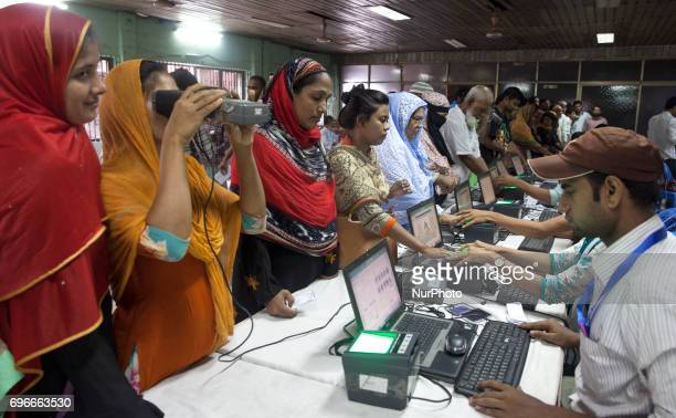 An Election Commission staff scanning the iris and fingerprint of a voter at a temporary camp set up at Old part of Dhaka Lalkuthi near the Councilor...