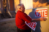 An election day volunteer places signs to direct voters to a polling station at Kenilworth School February 28 2012 in Phoenix Arizona Voters in this...