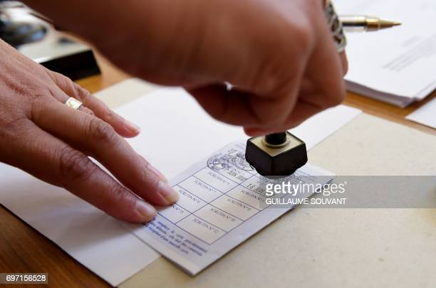 An election helper stamps a voting card at a polling station in Authon northern France on June 18 during the second round of the French parliamentary...