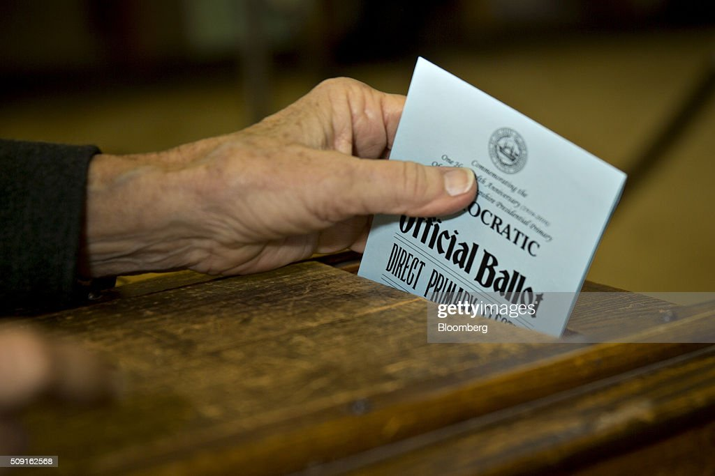 An election moderator places a Democratic ballot into a ballot box at the Bartlett town hall during the first-in-the-nation New Hampshire presidential primary in Bartlett, New Hampshire, U.S., on Tuesday, Feb. 9, 2016. Polls suggest that Donald Trump maintains a dominant lead against his Republican rivals in New Hampshire ahead of today's primary. Photographer: Andrew Harrer/Bloomberg via Getty Images