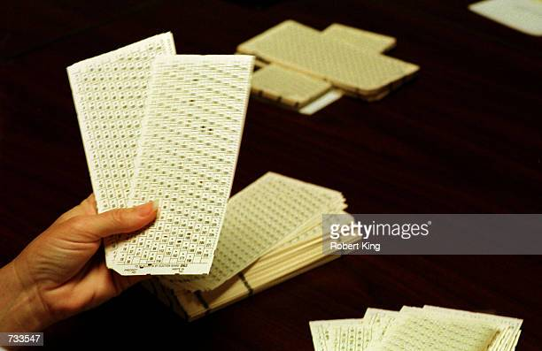 An election observer inspects and counts ballots during the hand recount of presidential ballots November 19 2000 at the Broward County Emergency...