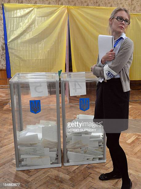 An election observer of the Organization for Security and Cooperation in Europe stands in front of ballot boxes prior to ballot counting at a polling...