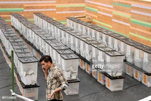 TOPSHOT An election observer talks on the phone next to ballot boxes during the count votes process in Tirana on June 26 2017 of the general election...