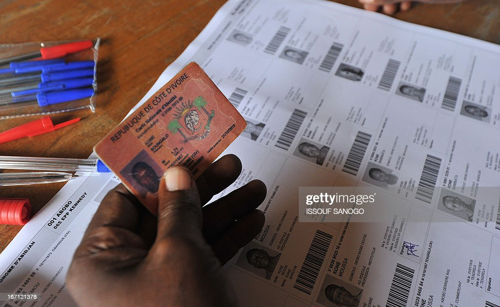 An election officer checks a ID card at a polling station on April 21, 2013 in the Abobo suburb of Abidjan. Ivorians voted Sunday in local elections seen as a trial run for a presidential poll in 2015 amid high tensions as the party of former president Laurent Gbagbo boycotted the poll. AFP PHOTO / ISSOUF SANOGO