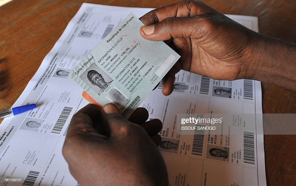 An election officer checks a voting card at a polling station on April 21, 2013 in the Abobo suburb of Abidjan. Ivorians voted Sunday in local elections seen as a trial run for a presidential poll in 2015 amid high tensions as the party of former president Laurent Gbagbo boycotted the poll.