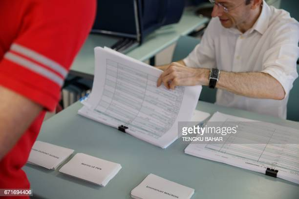 An election official checks a registry as ballot papers marked with the names of presidential candidates are seen as French nationals residing in...