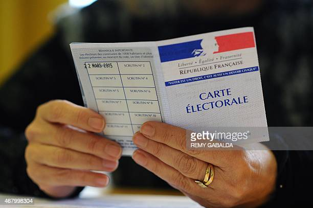 An election official checks a voter registration card on March 29 2015 during the second round of the French departemental elections in the...