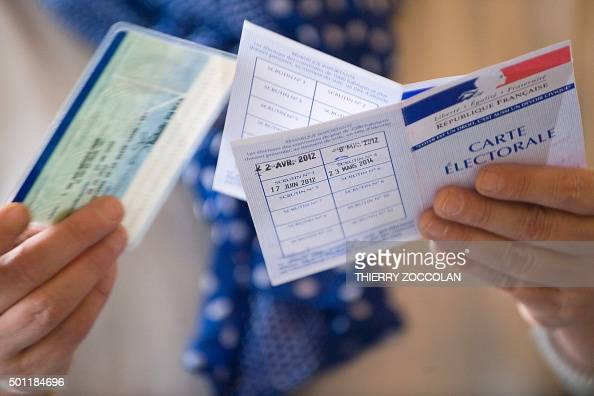 An election official controls the identity of a voter at a polling station in Le Puy en Velay central eastern France during the second round of the...