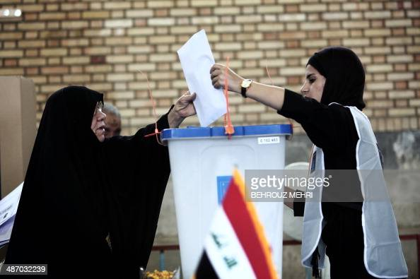 An election official helps an Iraqi woman residing in Iran to cast her ballot at a polling station in southern Tehran on April 27 2014 Iraqi...