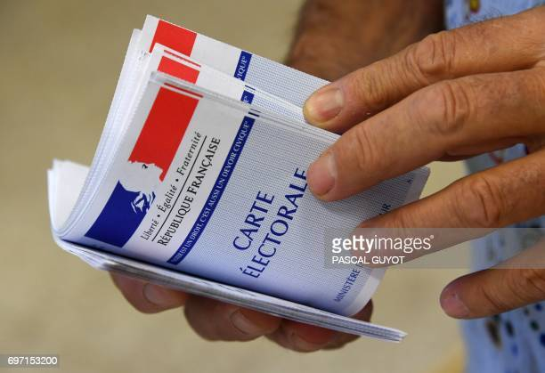 An election official holds electoral cards at a polling station on June 18 2017 in Gallician southern France during the second round of the French...