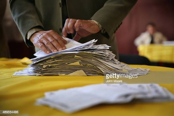 An election official sorts through a pile of 'yes' votes for independence for eastern Ukraine next to a short stack of ballots marked 'no' at a...