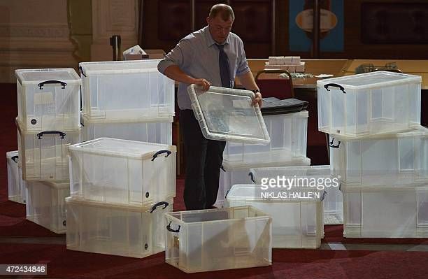 An election official stacks plastic boxes at a vote counting centre in Margate southeast England on May 7 2015 in preparation for the arrival of the...