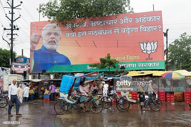 An election poster featuring Indian Prime Minister Narendra Modi stands above market stalls in Patna Bihar India on Saturday July 11 2015 Anyone...