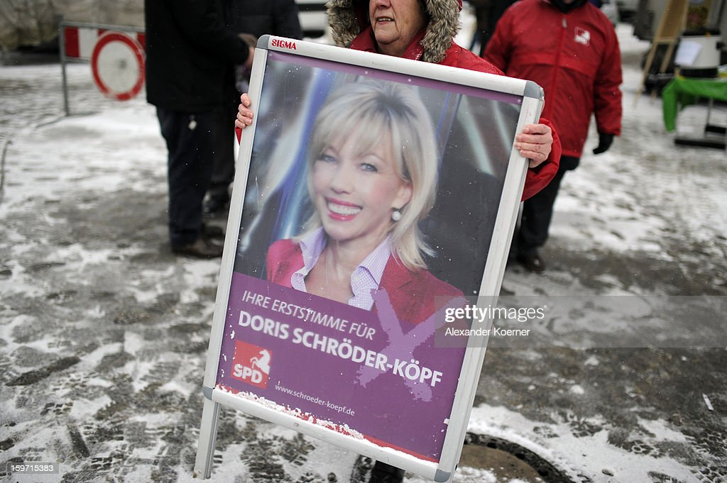 An election worker carries a poster of Doris Schroeder-Koepf, the wife of former German Chancellor Gerhard Schroeder, at a local weekly market in Hanover-Doehren. Schroeder-Koepf distributes flowers and speaks to passers-by while campaigning in elections in the state of Lower Saxony on January 18, 2013 in Hanover, Germany. Schroeder-Koepf is running for office as a member of the German Social Democrats (SPD) to represent her local district in election scheduled for this Sunday.