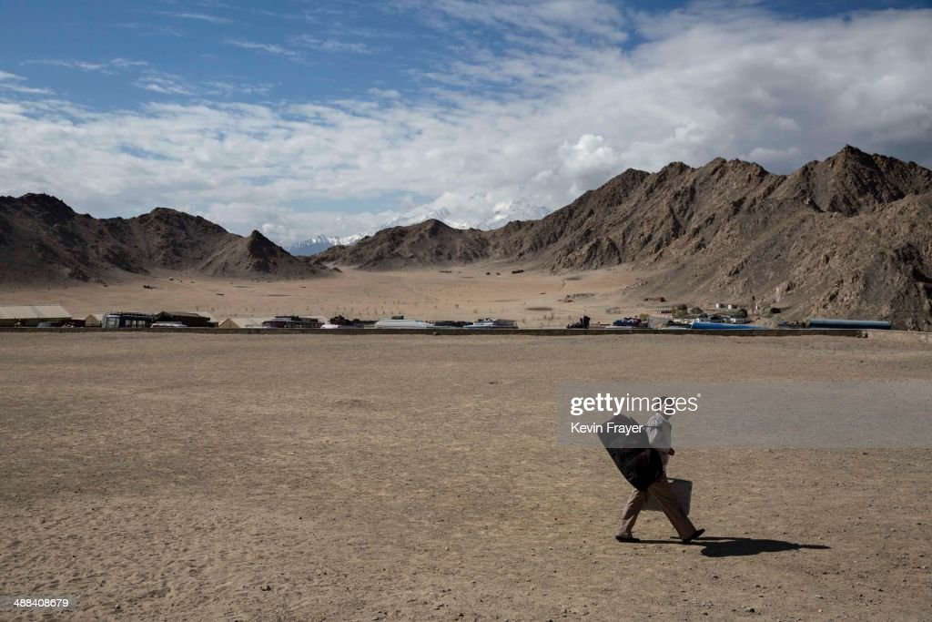 An election worker carries a voting machine and his overnight bag as he leaves a central collection point to head for a polling station, on May 6, 2014 in Leh, Ladakh, India. India is in the midst of a nine phase election that began on April 7th and ends on May 12th. Ladakh voters will vote on May 7th.