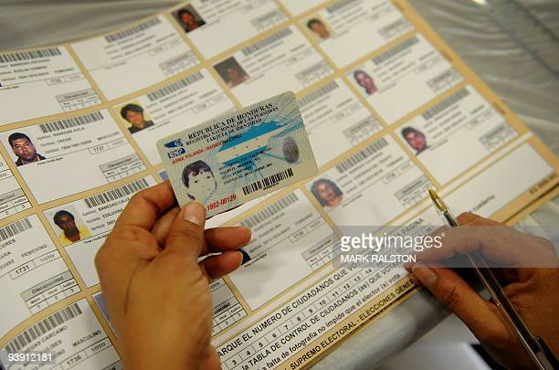 An election worker checks the identity of a voter in the Honduran Presidential election at a polling center set up in Los Angeles on November 29 2009...