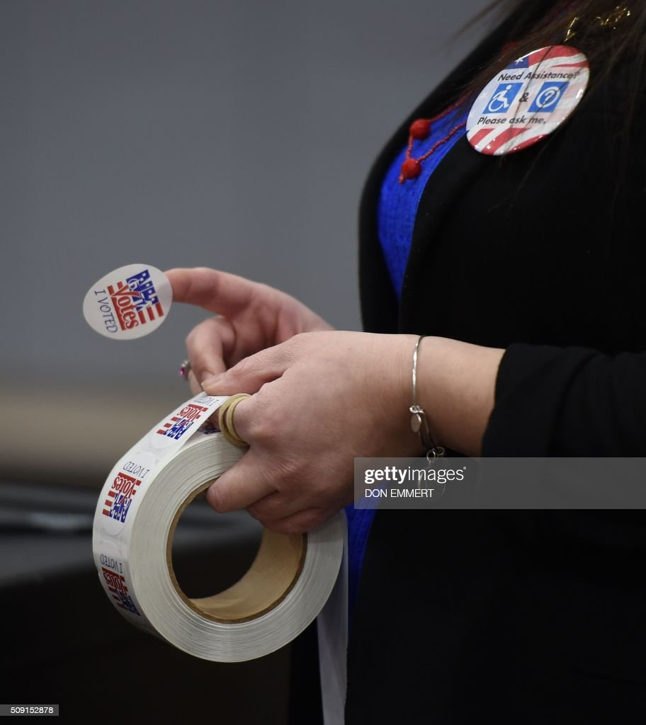 An election worker hands out stickers to voters afer casting their ballots at Belmont High School February 9, 2016 in Belmont, New Hampshire. / AFP / Don EMMERT