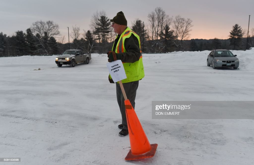 An election worker moves a parking sign in preparation for voting at Belmont High School February 9, 2016 in Belmont, New Hampshire. Voting began in New Hampshire on February 9 in the first US presidential primary, where Donald Trump leads the packed Republican field and Bernie Sanders was polling ahead of Hillary Clinton. Despite its small size New Hampshire's spot on the electoral calendar gives it special importance in the long state-by-state battle to select the Republican and Democratic candidates who will go head to head for the White House. / AFP / Don EMMERT