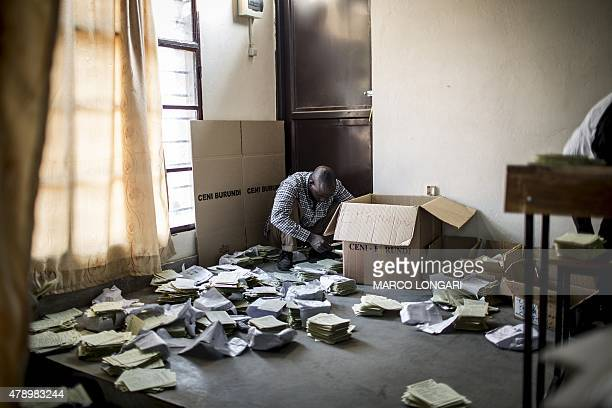 An electoral commission official arranges unclaimed electoral cards at a polling station in the opposition stronghold of Musaga Bujumbura on June 29...