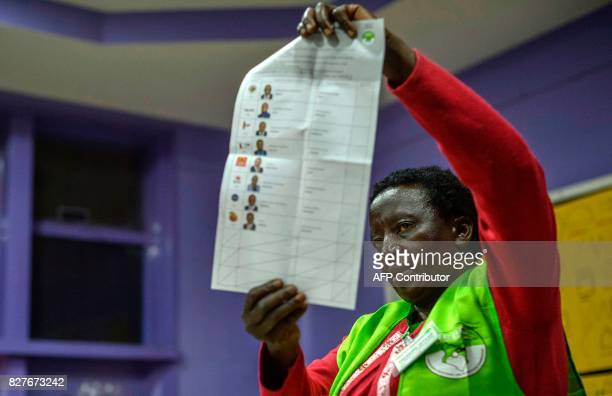 An electoral Commission official counts ballots at a polling station in Nairobi on August 8 2017 Kenyans thronged polling stations to vote in...