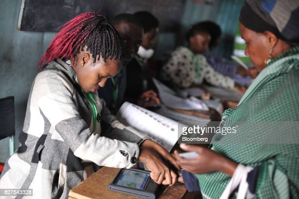 An electoral commission official registers a voter using a fingerprint scanner in a polling station at the Don Bosco center in Kiserian Kenya on...