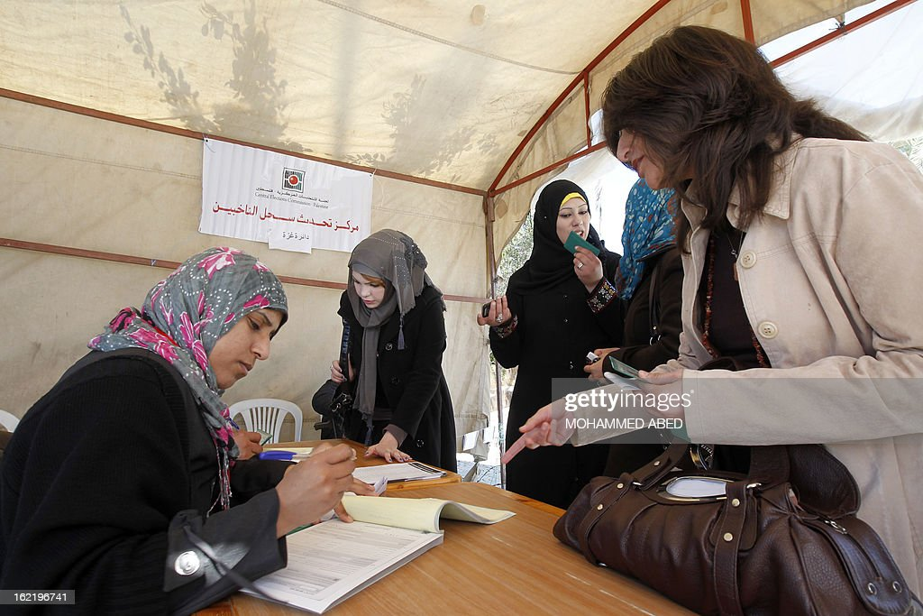 An electoral commission official registers Palestinian women at a registration tent set-up along a street in Gaza City on February 20, 2013. Palestinian electoral officials are updating voter rolls in the West Bank and Gaza in a vital step towards eventual elections. AFP PHOTO/MOHAMMED ABED
