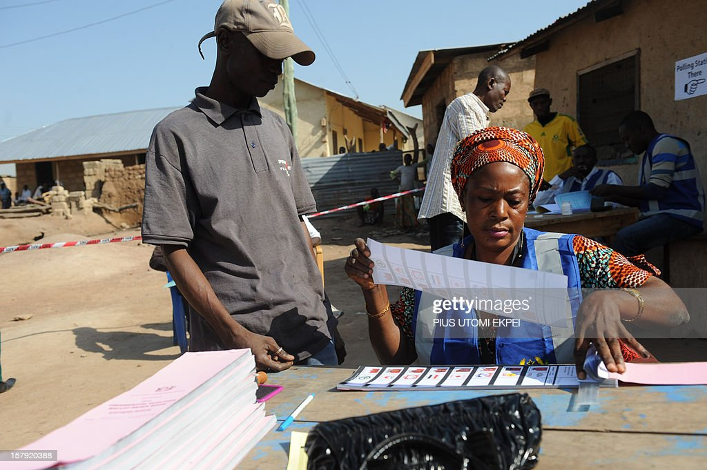 An electoral officer gives ballot papers to a voter upon his arrival at Bole polling station in the northern region on December 7, 2012