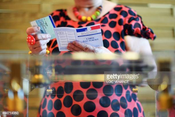 An electoral official checks the ID cards of a voter at a polling station in Vertou western France during the first round of the French legislative...