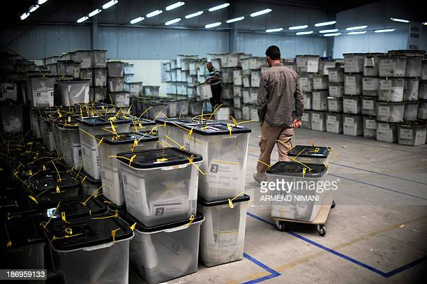 An electoral official pulls ballot boxes at a counting center near Pristina on November 5 2013 Polls opened on November 3 in key local elections in...