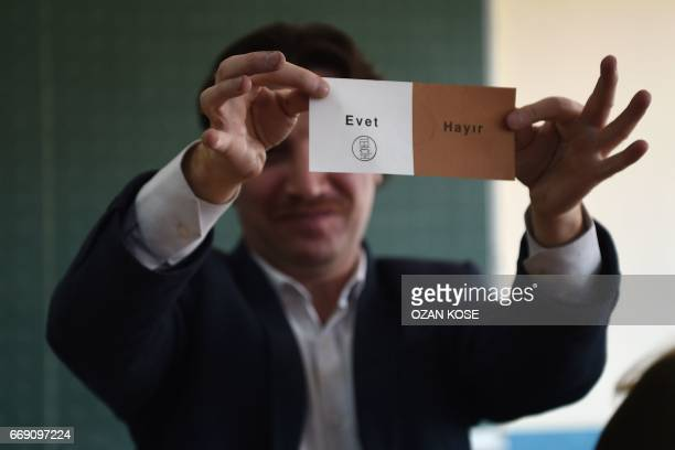 An electoral official shows a 'Yes' vote as they count ballot boxes after the polls closed during the referendum on expanding the powers of the...