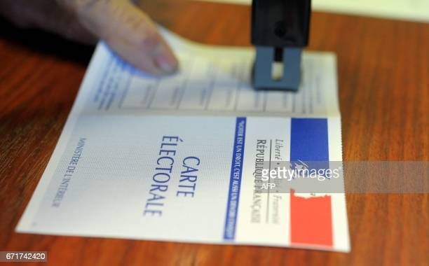 An electoral official stamps an electoral card at a polling station in Landevenec western of France during the first round of the presidential...