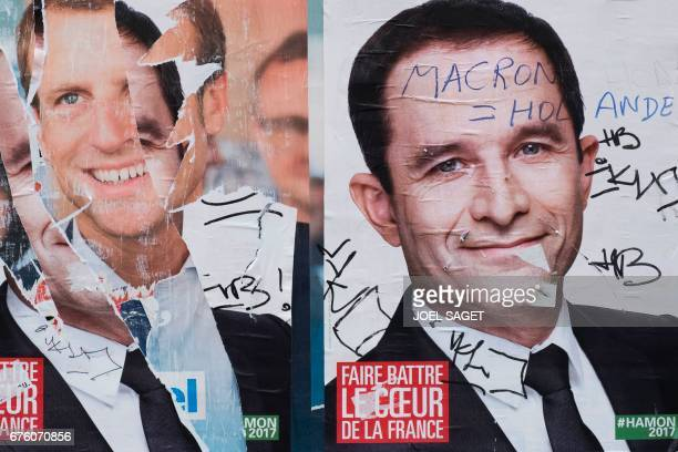 An electoral poster of French presidential election candidate for the En Marche movement Emmanuel Macron is damaged next to an electoral poster of...