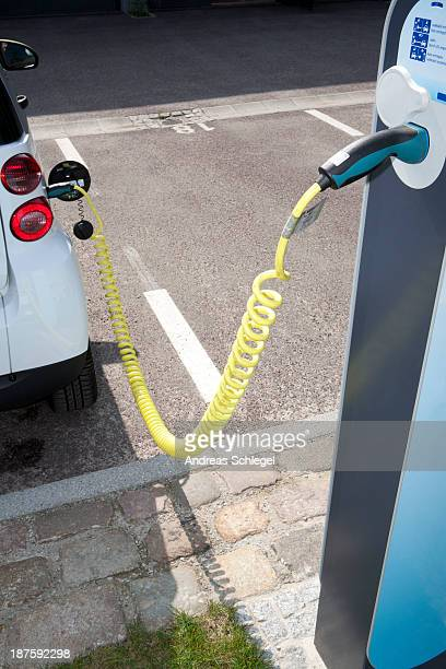 An electric car recharging at a charging station