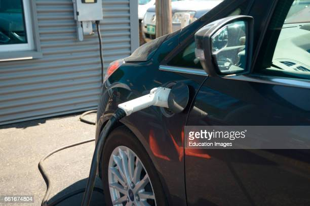 An electric car sits at its charging station as a charger ramps up the battery making ready to travel
