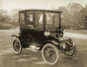 An electric car with two women seated inside is pictured in a photograph circa 1912