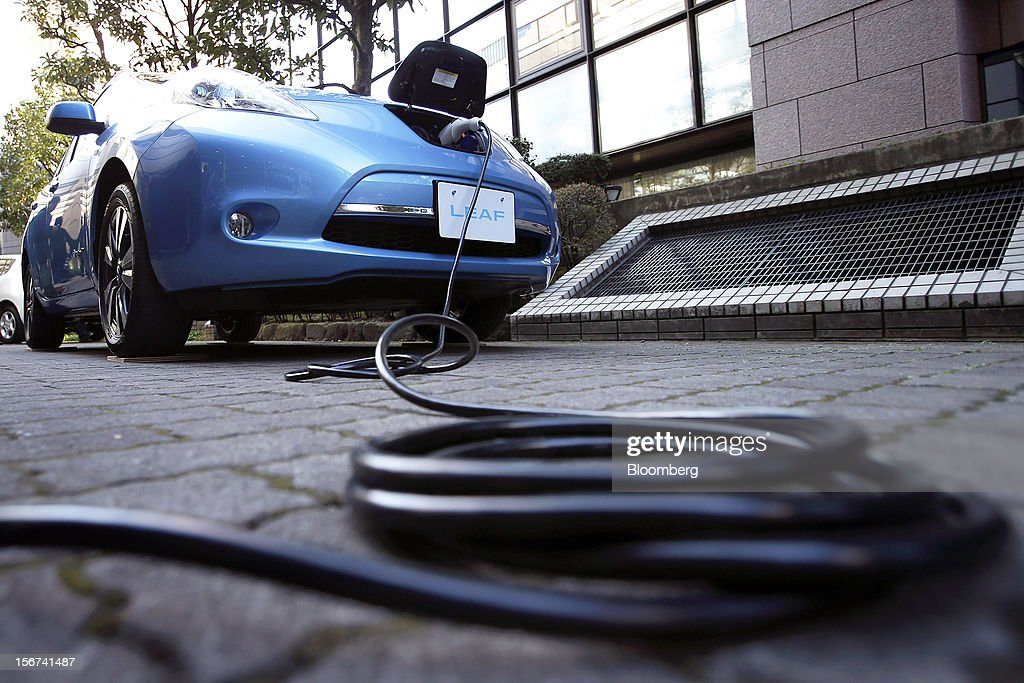 An electric charging cable is seen connected to the updated Nissan Leaf electric vehicle (EV) produced by Nissan Motor Co. during a news conference in Japan, Tokyo, on Tuesday, Nov. 20, 2012. Nissan Motor Co., Japan's second-largest carmaker, introduced a cheaper version of the Leaf electric vehicle to lure cost-conscious buyers as sales of the original model lag behind the company's target. Photographer: Kiyoshi Ota/Bloomberg via Getty Images