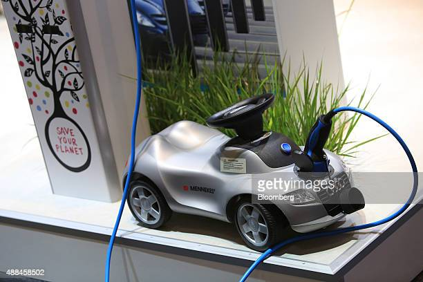 An electric charging plug sits connected to a toy car at the Mennekes Elektrotechnik GmbH exhibition stand during the IAA Frankfurt Motor Show in...