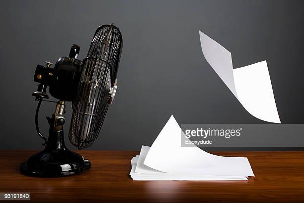 An electric fan blowing a stack of paper