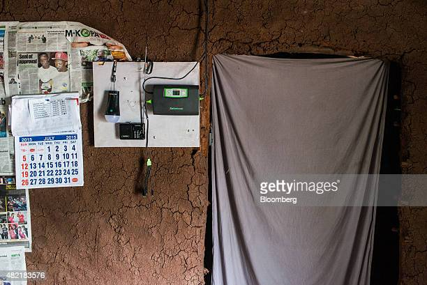 An electric LED light and electrical control unit operated by Safaricom Ltd sits on a mud wall in a home powered by MKopa solar technology in Ndela...